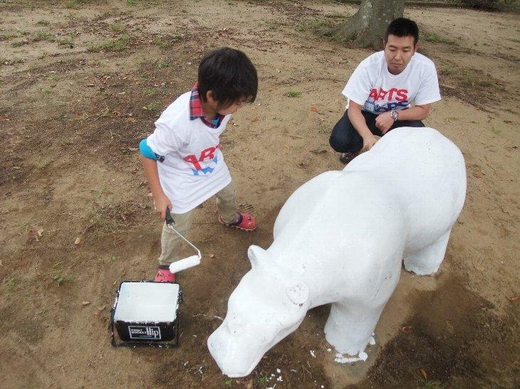 ペンキの下地を塗る子供